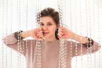 Smiling brunette woman looking at camera pushing interior curtains of glass beads with her hands