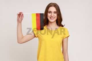 Portrait of pleasant looking teenager girl in yellow T-shirt holding Germany flag, celebrating Day of Germany - 3th October, expressing positive.