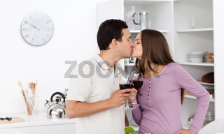 Cute couple kissing with glasses of red wine in their hands
