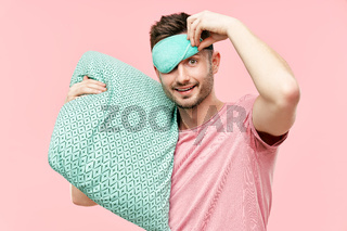 Funny cheerful man in sleeping mask holding pillow in hands looking to camera