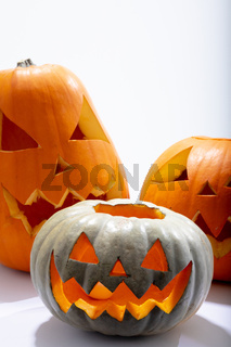 Composition of three halloween carved pumpkins with copy space on white background
