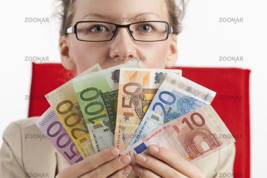 Frau mit Brille blickt über Fächer aus Banknoten