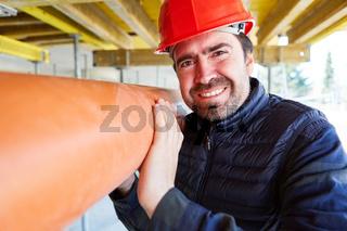 Handwerker trägt ein Wasserrohr auf der Baustelle