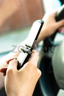 A phone in the hand os a woman who is driveing