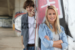 Attractive couples stood by graffiti covered wall