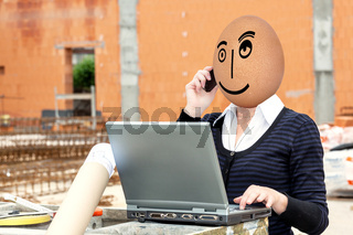 Woman with egghead and laptop at the construction site