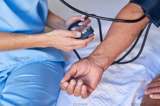Hände von Patient und Pfleger beim Blutdruck messen
