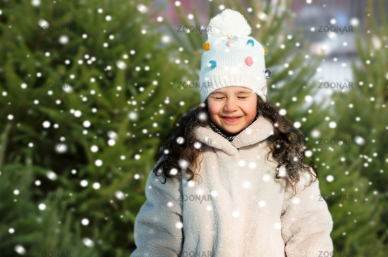 happy little girl in winter clothes over snow