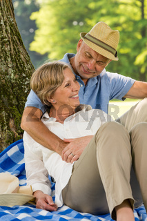 Elderly wife and husband hugging in park