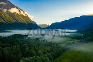 Morning mist over the valley among the mountains in the sunlight. Fog and Beautiful nature of Norway aerial footage.
