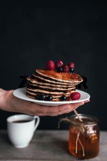 Pancakes with berries and honey on white plate on human hand, coffee cup, jar