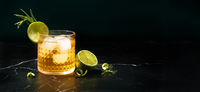 Alcoholic or non-alcoholic cocktail with lime and rosemary on dark marble table