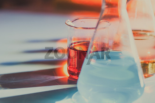 Illuminated laboratory flask filed with colorful chemical solutions with shadows on the table. Laboratory, science, chemistry... consept.