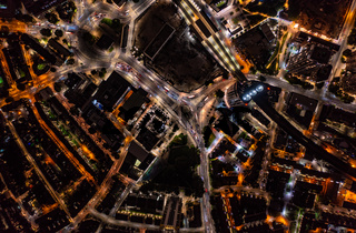 Birds eye view of tall financial and commercial buildings with shadow and cars moving on city street during night with illuminated lights in London city