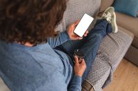 Rear view of disabled man holding coffee cup using smartphone with copy space on couch at home