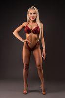 Athletic blond woman posing in lingerie in dark studio