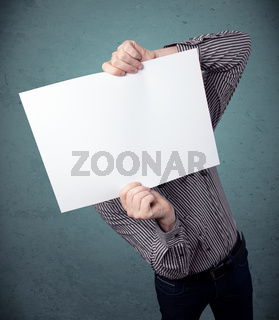 Businessman holding in front of his head a paper with copy space