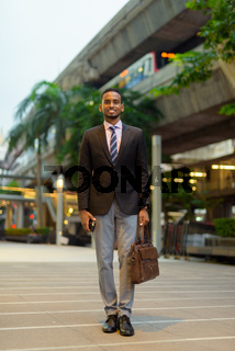 Full length portrait of handsome young African businessman smiling outdoors in city