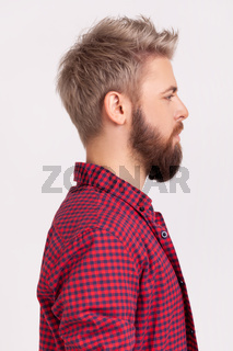 Profile portrait of confident bearded male with blond hair wearing red plaid shirt looking to side space with serious attentive face
