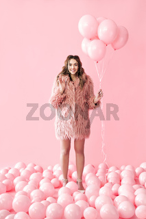 Full length portrait of happy glamour woman with pink balloons on pink pastel background