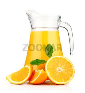 Orange juice in pitcher and oranges.