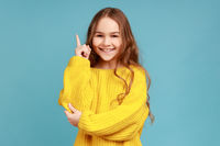 Portrait of little girl points finger up, looking inspired by genius thought, showing good idea sign