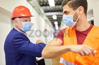Chef und Lagerarbeiter bei Ellenbogen Begrüßung