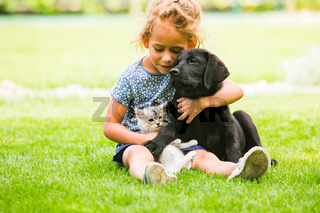 Little girl taking care of her dog and cat
