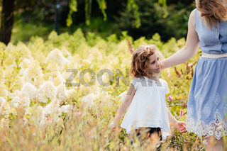 Young mother and little daughter choosing plants