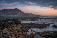 A Guarda beautiful sea landscape rock beach with city on the foreground at sunset, in Spain