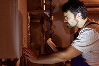 Heizungsmonteur mit Checkliste kontrolliert Gasheizung