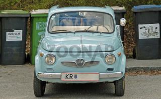 Alter österreichischer Kleinwagen vor Abfallkübeln