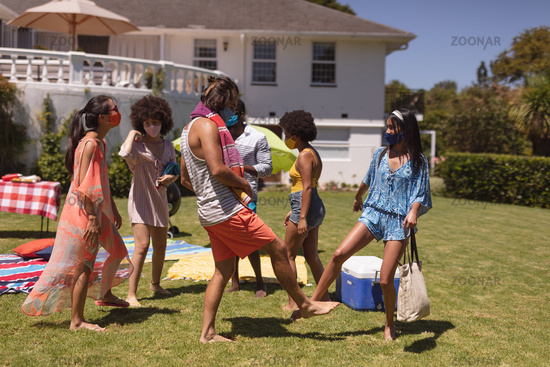 Group of diverse friends wearing face masks bumping legs at a pool party