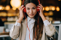 Young woman with headphones listen music while sitting in cafes