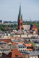 Church of the St. Catherine surrounded by buildings under the sunlight and a blue sky in Torun, Poland