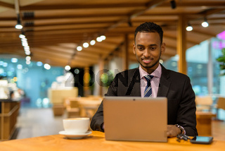 Young African businessman in coffee shop using laptop computer