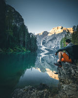 Man at Lago di Braies Lake in Italy with a perfect Reflection of the Mountain