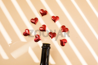 Bottle of wine and red hearts over morning shadow overlay.