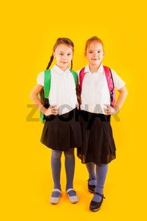 Two friendly schoolgirls in uniform are holding their hands on belt