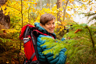 Woman hiker is taking a selfie in the autumn forest