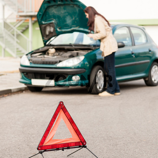 Woman trying to fix her broken car