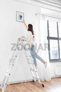 woman on ladder decorating home with art
