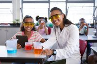 Portrait of african american female teacher and girl smiling during science class at laboratory