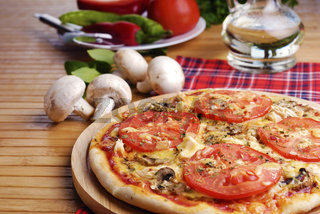 Pizza with mushrooms and tomatos
