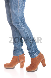 legs in jeans wearing leather fashion boots isolated on white background (walking pose)