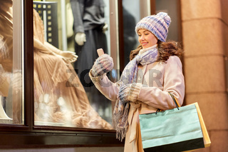 woman with shopping bags and smartphone in winter