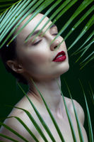 Romantic female with closed eyes on a background of palm leaves.