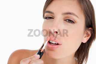 Concentrated young woman using a lip gloss brush to apply make-up