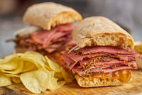 Pastrami sandwhich with delicious meet on baguette bread with chedder cheese, onion