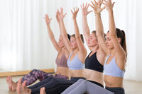 Group of young sporty attractive women in yoga studio, practicing yoga lesson with instructor.